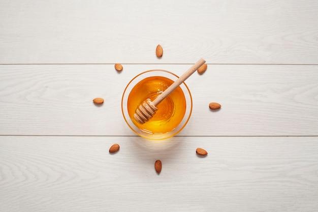 Vista dall'alto miele fatto in casa circondato da mandorle Foto Gratuite