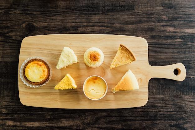 Vista dall'alto molti tipi di fette di cheesecake alla crema brulée al mascarpone, crostate al formaggio sul tagliere di legno, gusto morbido e ricco di latte. Foto Premium