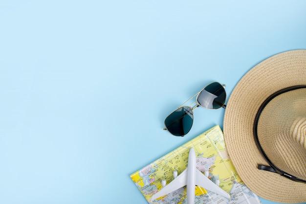 Vista dall'alto. occhiali da sole e un cappello con una mappa su sfondo blu Foto Premium