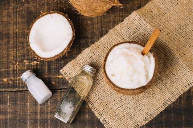 Vista dall'alto olio di cocco con composizione di cocco Foto Gratuite