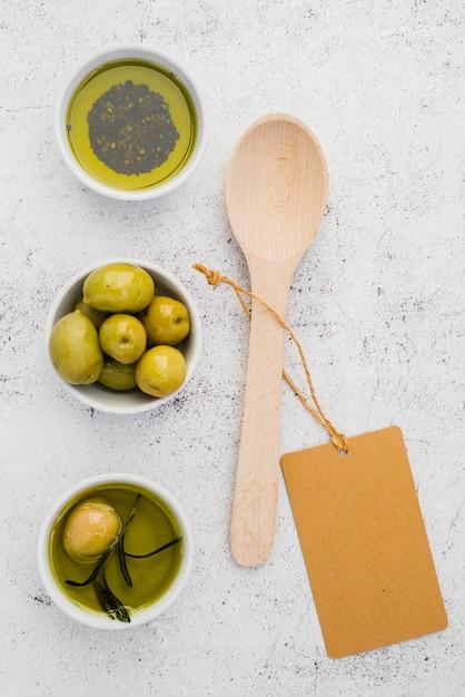 Vista dall'alto olive e olio con cucchiaio Foto Gratuite