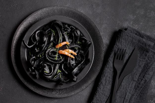 Vista dall'alto pasta di gamberi neri e posate nere Foto Gratuite