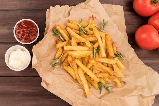 Vista dall'alto patatine fritte sul sacchetto di cartone con ketchup Foto Gratuite