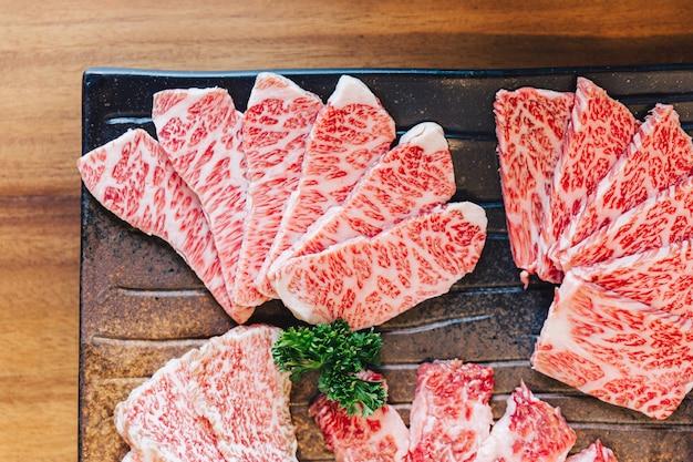 Vista dall'alto ravvicinata di premium rare slices molte parti di manzo wagyu a5 con trama marmorizzata. Foto Premium