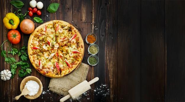 Vista dall'alto, sopra di pizza ai frutti di mare e ingredienti, verdure da decorare intorno come aglio peperoncino pomodoro peperoncino. sullo sfondo del tavolo di legno. Foto Premium