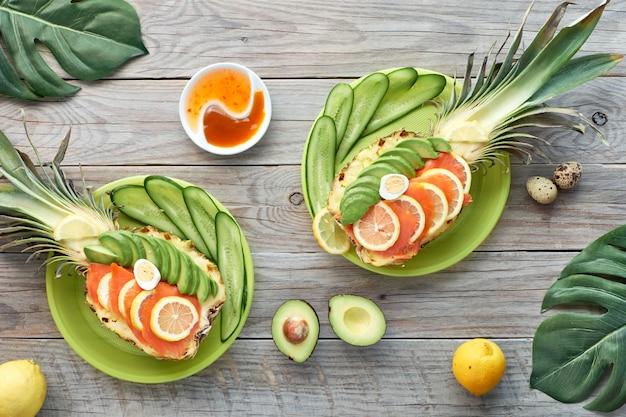Vista dall'alto su barche di ananas con fette di salmone affumicato e avocado con uova di limone e quaglia, piatto giaceva sul vecchio tavolo di legno Foto Premium