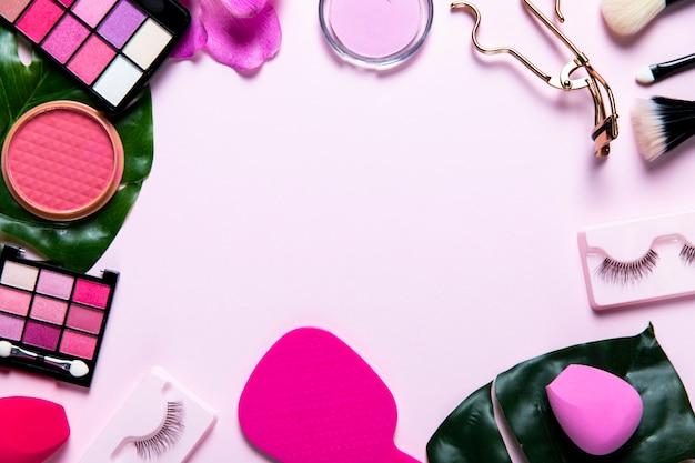 Vista dall'alto su cosmetici su sfondo rosa con spazio di copia Foto Gratuite