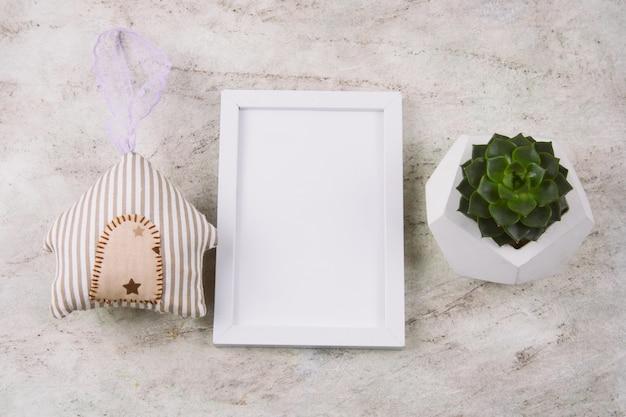 Vista dall'alto succulente in vaso di cemento, casa giocattolo farcito e bianco finto telaio su un tavolo di marmo Foto Premium