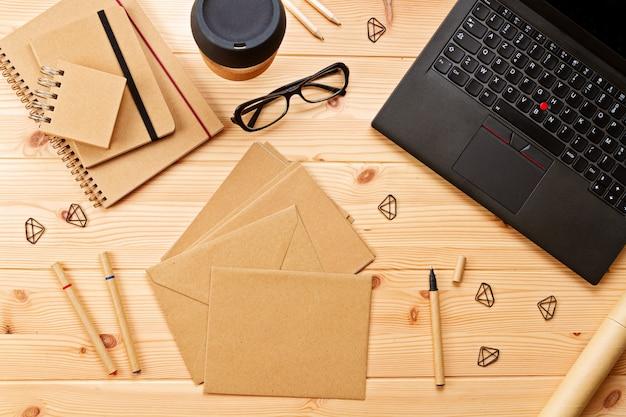 Vista dall'alto sul posto di lavoro con laptop e articoli per ufficio Foto Premium