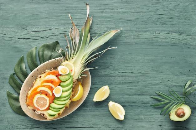 Vista dall'alto sulla barca di ananas con salmone affumicato, avocado, limone e uova di quaglia, copia-spazio Foto Premium