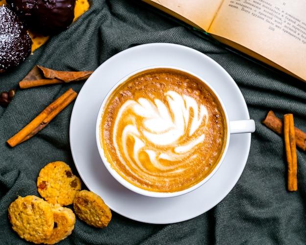 Vista dall'alto tazza di cappuccino con biscotti e un libro sul tavolo Foto Gratuite