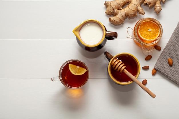Vista dall'alto tazza di tè con miele e fetta d'arancia Foto Gratuite