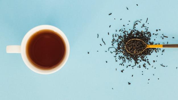Vista dall'alto tazza di tè con un cucchiaio pieno di foglie secche Foto Gratuite