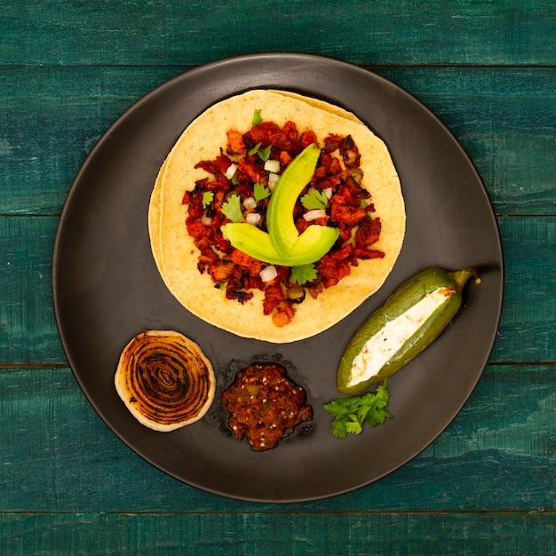 Vista dall'alto tortilla in un piatto con ingredienti Foto Gratuite