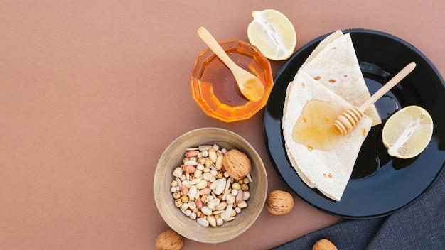 Vista dall'alto tortillas su un piatto con miele Foto Gratuite