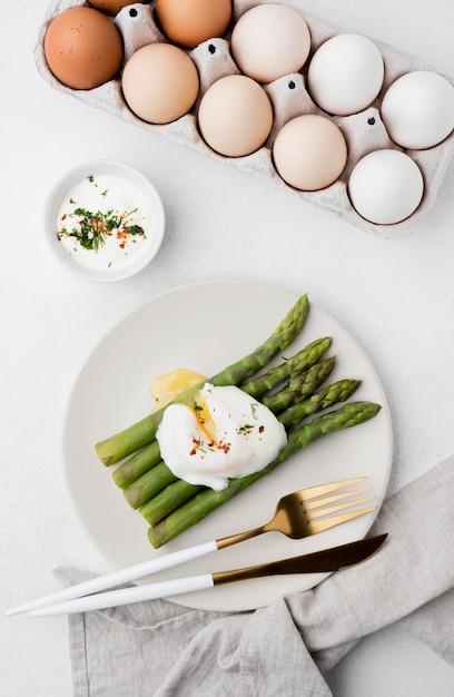 Vista dall'alto uovo fritto con asparagi Foto Gratuite