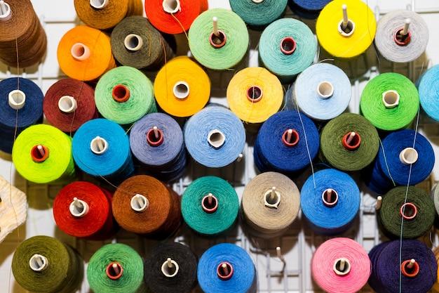 Vista dall'alto varietà di bobine grandi e usate di fili colorati per cucire. sartoria tema sfondo, tessuti e abbigliamento industria concetto. messa a fuoco selettiva, spazio per il testo Foto Premium