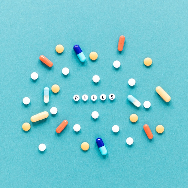 Vista dall'alto varietà di pillole colorate sul tavolo Foto Gratuite