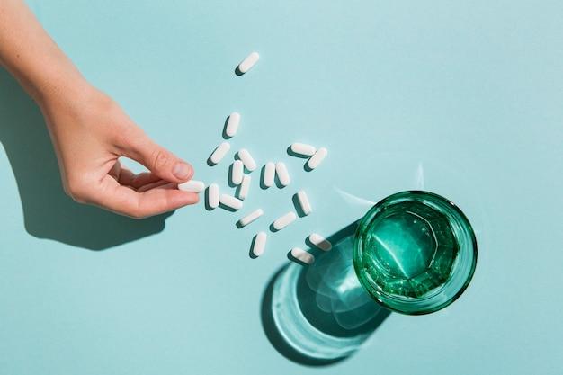 Vista dall'alto vetro con acqua e medicina sul tavolo Foto Gratuite