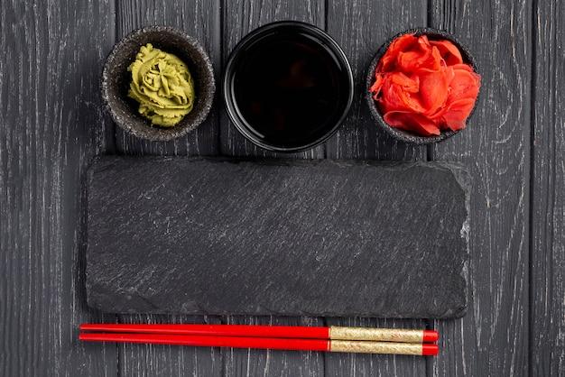 Vista dall'alto wasabi e bacchette di salsa di zenzero e salsa di soia Foto Gratuite