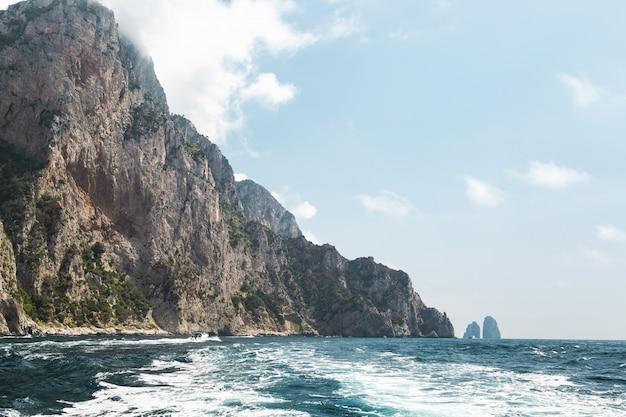 Vista dalla barca sulla costa dell'isola di capri e formazione rocciosa oceanica di faraglioni. Foto Premium