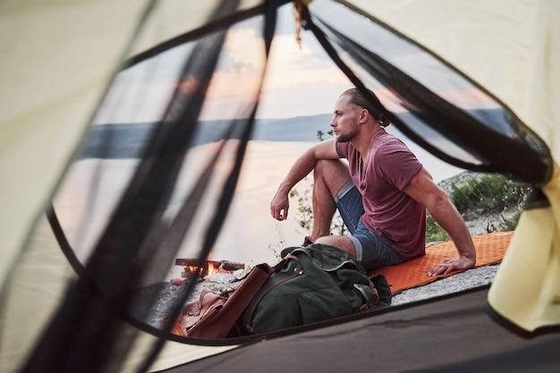 Vista dalla tenda del viaggiatore con lo zaino che si siede in cima alla montagna che gode della vista costeggia un fiume o un lago. Foto Gratuite