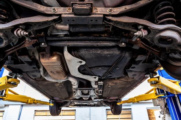 Vista del carrello dell'automobile quando sollevato su ascensore idraulico in un'officina Foto Premium