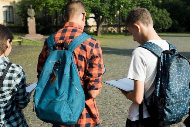 Vista del colpo medio indietro di lettura degli studenti della high school Foto Gratuite