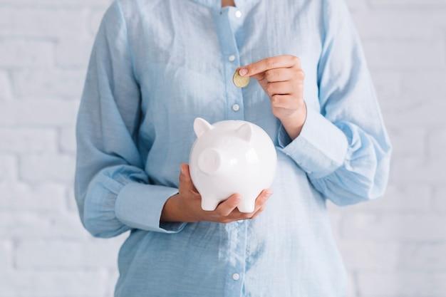 Vista del midsection della mano di una donna che inserisce moneta nel porcellino salvadanaio bianco Foto Gratuite