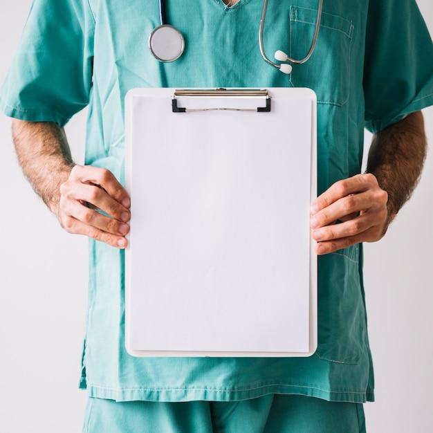 Vista del midsection di una lavagna per appunti maschio della tenuta di medico con i white paper in bianco Foto Gratuite