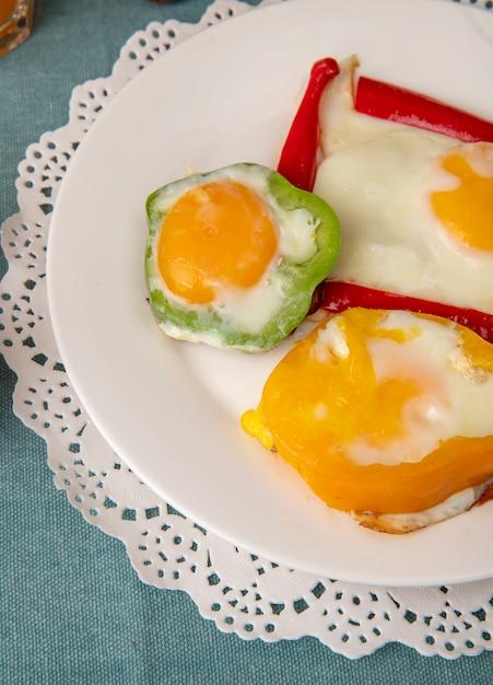 Vista del primo piano del piatto stabilito della prima colazione con le uova e peperoni sul centrino di carta su fondo blu Foto Gratuite