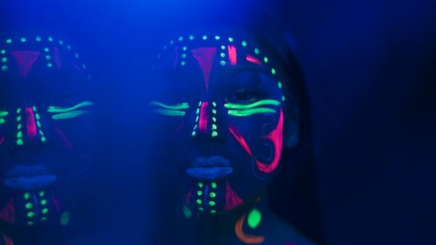 Vista del primo piano della donna con trucco fluorescente Foto Gratuite