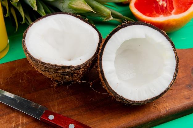 Vista del primo piano della noce di cocco e del coltello del mezzo taglio sul tagliere con altri agrumi su fondo verde Foto Gratuite