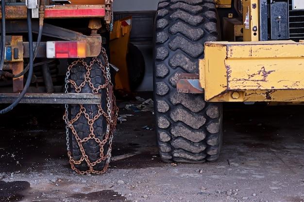 Vista del primo piano della ruota del camion con le catene arrugginite di sicurezza sulla strada Foto Premium