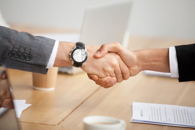Vista del primo piano della stretta di mano, due uomini d'affari in vestiti che agitano le mani Foto Gratuite