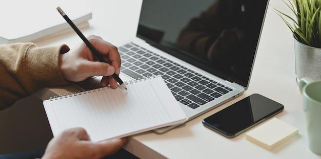Vista del primo piano delle free lance maschii che scrivono il suo taccuino dello ione di idea nella stanza comoda Foto Premium