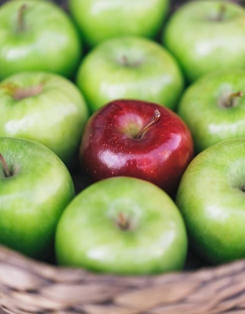 Vista del primo piano delle mele verdi sane e di una mela rossa in un cestino Foto Premium