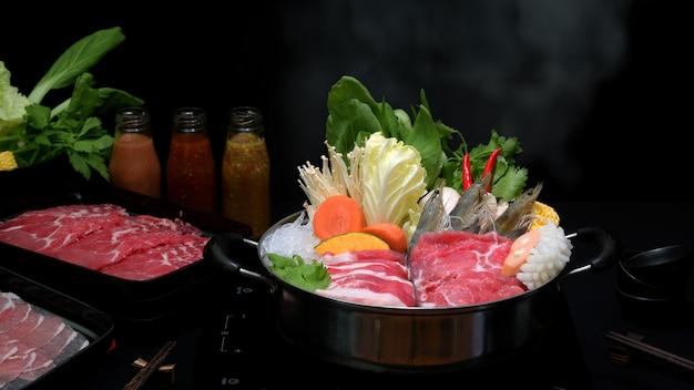 Vista del primo piano dello shabu di shabu in pentola calda con fondo nero, carne affettata fresca, frutti di mare e verdure Foto Premium