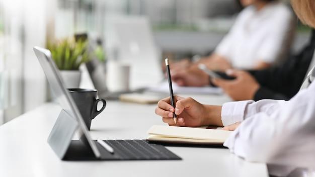 Vista del primo piano di giovane donna di affari che lavora al suo piano che scrive l'idea sul taccuino con la compressa digitale. Foto Premium