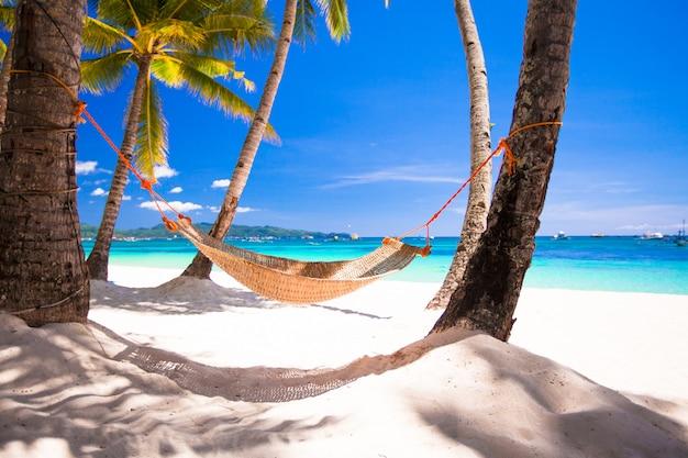 Vista dell'amaca accogliente della paglia sulla spiaggia bianca tropicale Foto Premium