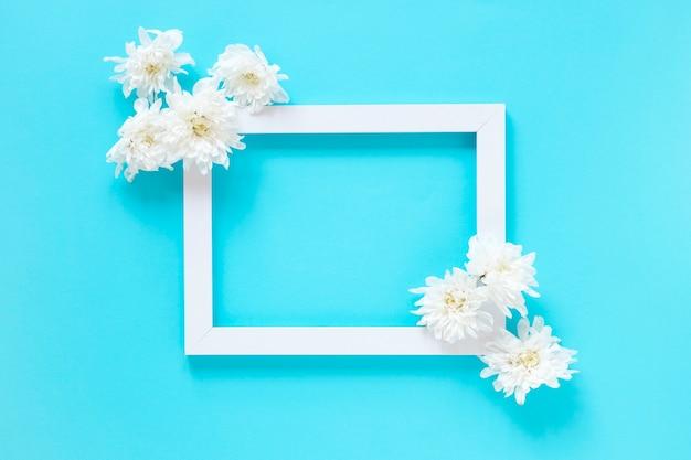 Vista dell'angolo alto dei fiori bianchi e della cornice in bianco su fondo blu Foto Gratuite