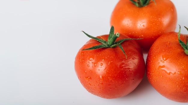 Vista dell'angolo alto dei pomodori rossi freschi su fondo bianco Foto Gratuite