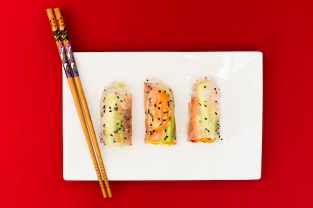 Vista dell'angolo alto dei rotoli di molla di verdure del riso decorati con i semi di sesamo sul piatto bianco con le bacchette di legno Foto Gratuite