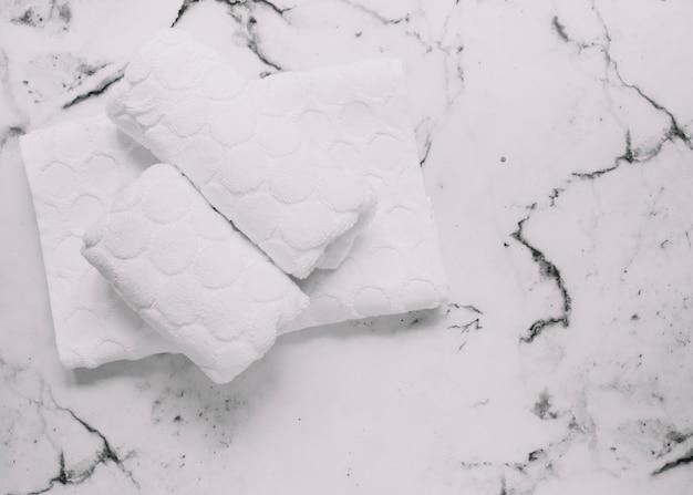 Vista dell'angolo alto dei tovaglioli bianchi su fondo di marmo Foto Gratuite