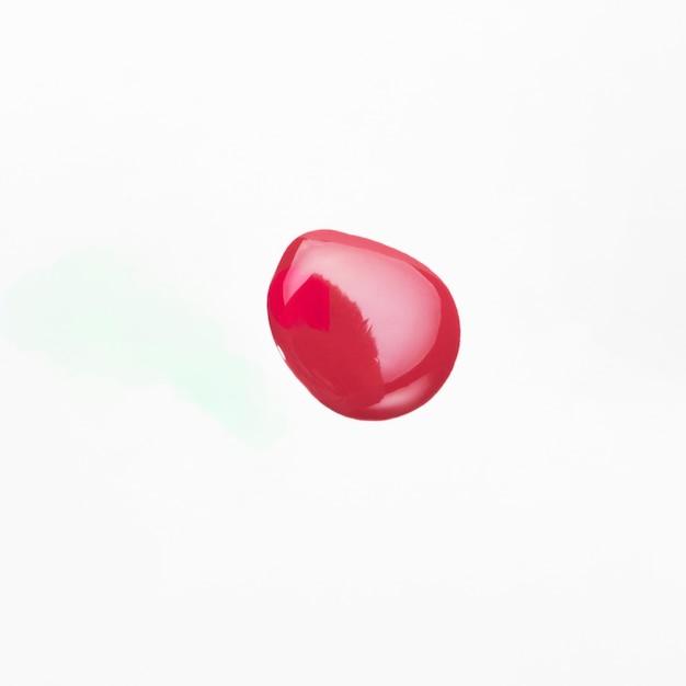 Vista dell'angolo alto del campione di goccia dello smalto rosso Foto Gratuite