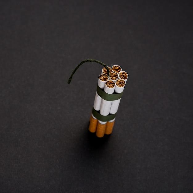 Vista dell'angolo alto del mazzo di sigaretta con lo stoppino contro la superficie del nero Foto Gratuite