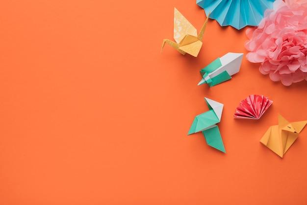 Vista dell'angolo alto del mestiere di arte di carta di origami sulla superficie arancione Foto Gratuite