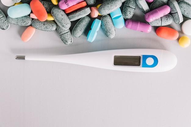 Vista dell'angolo alto del termometro e pillole variopinte sul contesto bianco Foto Gratuite