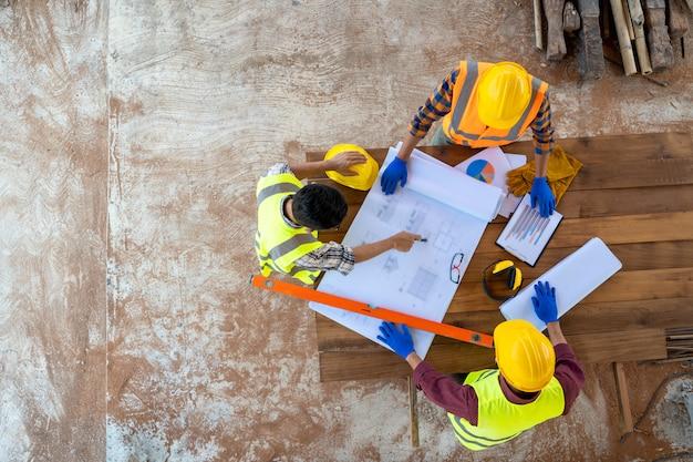 Vista dell'angolo alto dell'ingegnere e dell'architetto che discutono piano di costruzione al cantiere, gruppo di costruttori che hanno conversazione sul piano di costruzione. Foto Premium
