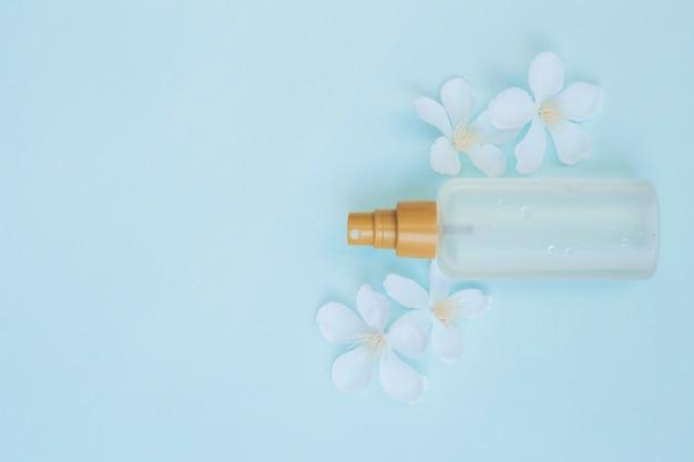 Vista dell'angolo alto della bottiglia di profumo con i fiori bianchi su fondo blu Foto Gratuite